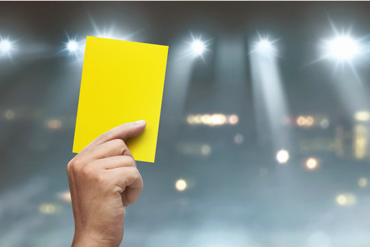 Hand of referee with yellow card
