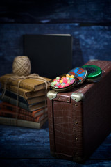 Old suitcase with sweets and books in the dark