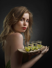 Young attractive woman with alcoholic drinks and slices of lime .