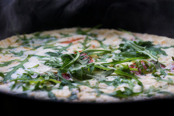 freshly cooked omelette with tomatoes and arugula hot in a pan, side view closeup