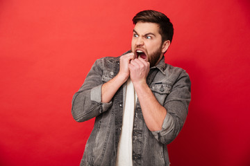 Image of frightened man 30s in jeans jacket looking aside on copyspace and biting his fists in horror or fright, isolated over red background