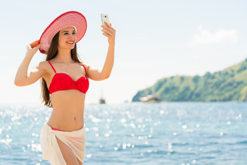 Beautiful young woman wearing a trendy striped hat while posing for a selfie picture on the beach during summer vacation in Flores Island, Indonesia