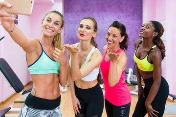 Four happy and beautiful women making a group selfie, to share with their virtual friends the joy of a healthy lifestyle in a trendy fitness club for ladies only