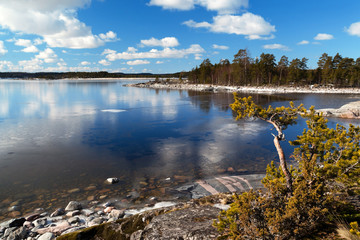 Reflection of blue sky and clouds in the freezing thin ice of Lake Ladoga in Karelia