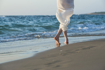 Beautiful woman in a white dress walking along the edge of the beach during a sunset. Close up on her legs.
