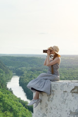 Girl sits on hill and takes pictures. Background of forest and meandering river on background