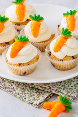Vanilla cupcakes with chocolate chips and cream cheese frosting decorated with carrot marmalade in a plate on a white stone background.