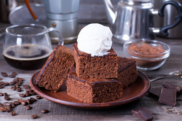 Chocolate cake with ice cream on plate on wood table.
