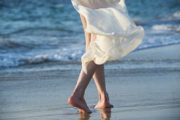 Beautiful woman in a white dress walking along the edge of the beach during a sunset. Horizon line