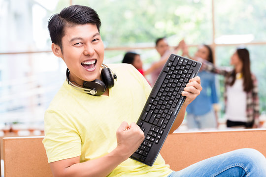 Portrait of young Chinese employee happy for his successful work on computer and for his contribution to the success of the team