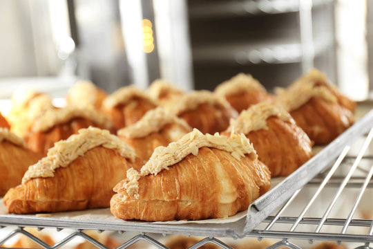 Shelf with delicious sweet croissants on tray in bakery