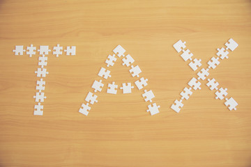 "wooden jigsaw puzzles with the word ""TAX"" on a wooden,Jigsaw business idea concept"