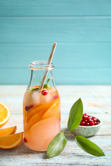 Bottle of tasty orange lemonade with cranberry on wooden table