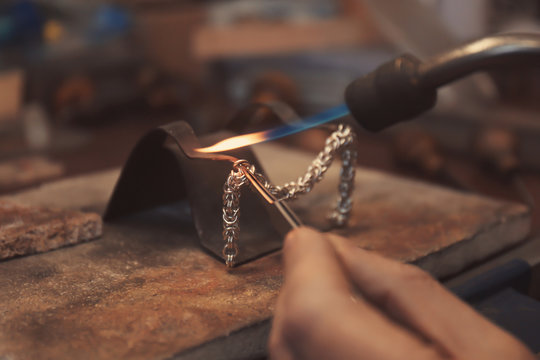 Jeweler working with blow torch, closeup
