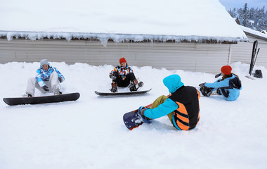 Group of friends taking snowboard lessons at snowy resort. Winter vacation