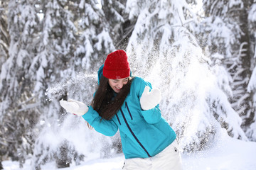Beautiful woman playing with snow in countryside. Winter vacation