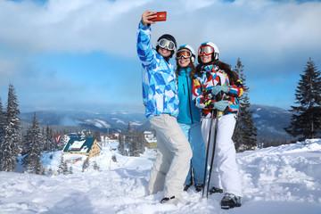 Happy friends taking selfie at snowy ski resort. Winter vacation