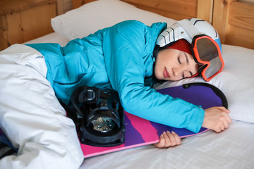 Woman in sports clothes with snowboard sleeping on bed. Winter vacation