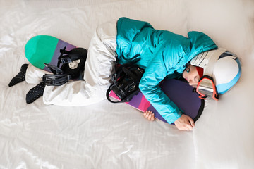 Keuken foto achterwand Wintersporten Woman in sports clothes with snowboard sleeping on bed. Winter vacation