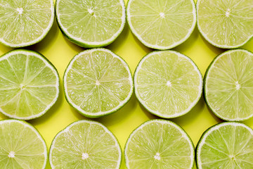 Background of limes split in half on yellow background