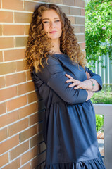 nice woman with chic curly hair stands near a brick wall in the backyard of her house.