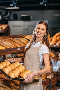 smiling shop assistant arranging loafs of bread in shopping market