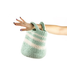 Woman's hand is holding big, colorful, crocheted basket isolated on white background.