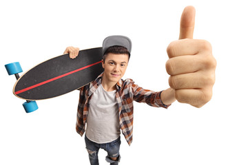 Teenage skater with a longboard making a thumb up gesture