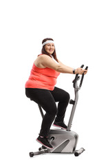 Overweight woman exercising on a stationary bike and looking at the camera