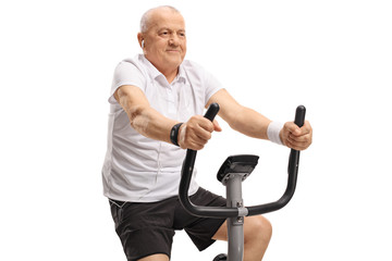 Mature man with earphones riding an exercise bike