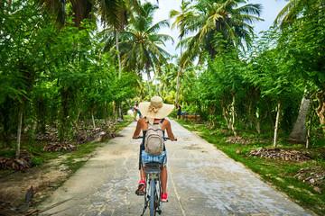 woman on a bicycle crosses vanilla plantations, dique island, se