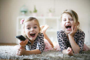 Little girls with remote at home.