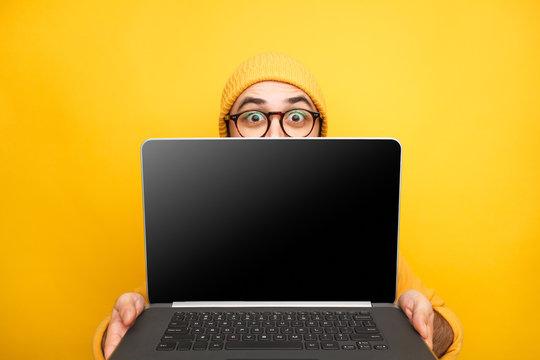 Playful man offering modern laptop
