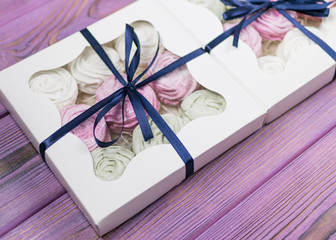 Marshmallow in a gift box on a wooden background. Sweet gift.