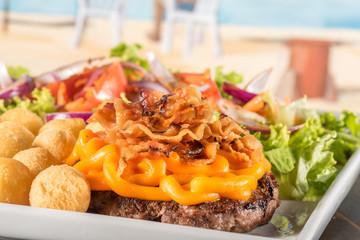 Delicioso hamburguer com cheddar e bacon, acompanhado de batata e salada.