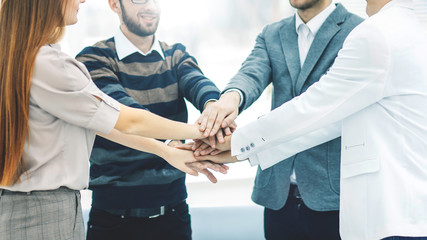 concept of success in business: friendly business team standing in a circle and joining his hands together