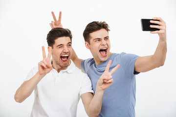 Portrait of two happy young men showing peace gesture