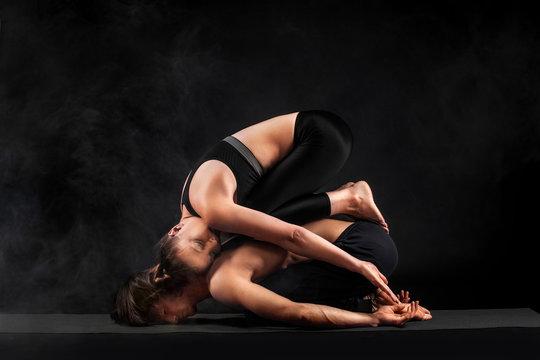Acroyoga. Young couple practicing acro yoga on mat in studio together. Couple yoga. Partner yoga. Black and white photo.