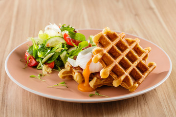 Savory Belgian waffles with egg poached, bacon and salad