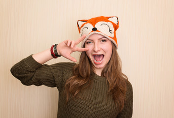 Close up studio portrait of cheerful hipster girl in funny fox hat.