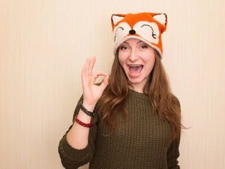 Portrait of a cheerful hipster girl in funny fox hat showing okay gesture.