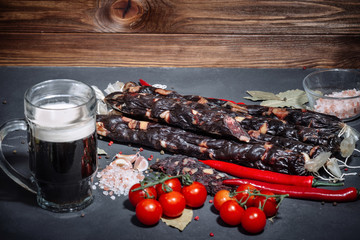 Delicious, smoked sausage on a dark board with beer and spices. Tasty Sausage handmade from natural ingredients.