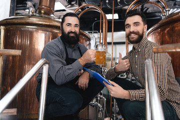 Two bearded brewers cooked lager at brewery of craft beer. Bearded brewer tasting beer.
