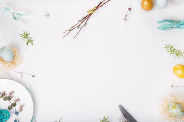 Easter table setting with gold and blue eggs and cutlery. Holidays background