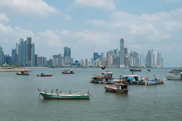 Boats near fish market and skyscraper skyline, coast of Panama City