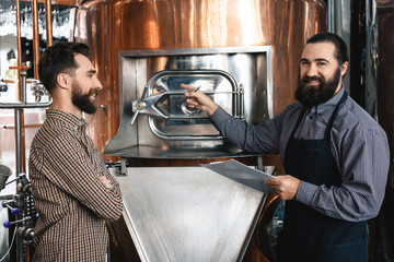 Two bearded brewers inspect equipment of brewery for production of craft beer. Brewing. Brewery.