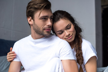 Young man and woman tenderly embracing in bedroom
