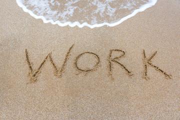 The word inscription work on the sand on the beach.