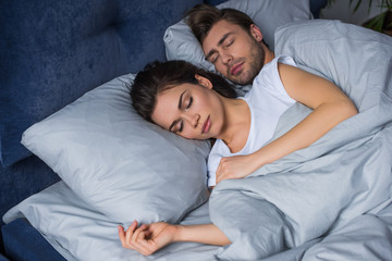 Young attractive couple hugging while sleeping in bed