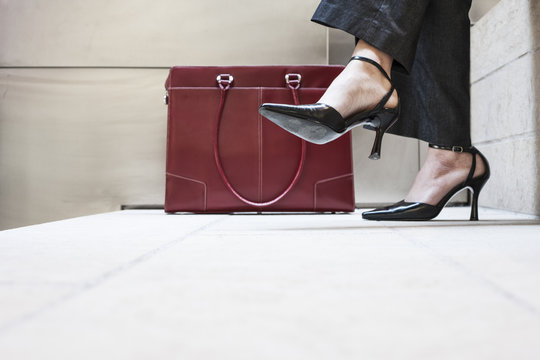Businesswoman's feet in high heeled shoes and her purse.